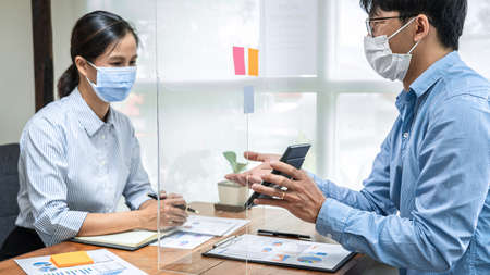 Asian business man showing investment amount on calculator to partner and discussion about new project while wearing protective face mask and sitting with table partition to keep social distance