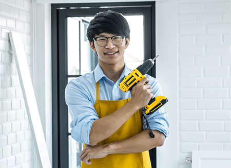 Portrait of Craftsman doing renovation work at home improvement with holding drill and interior design concept.