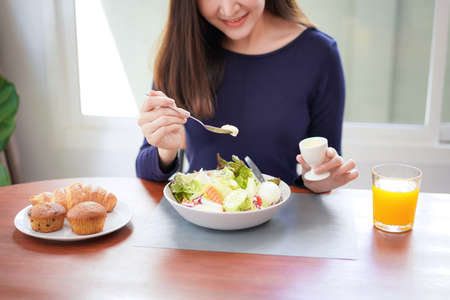Close up of young asian woman use a salad dressings spoon to mixing with fresh vegetable and drinking orange juice on wellness lifestyle for breakfast with healthy meal at home