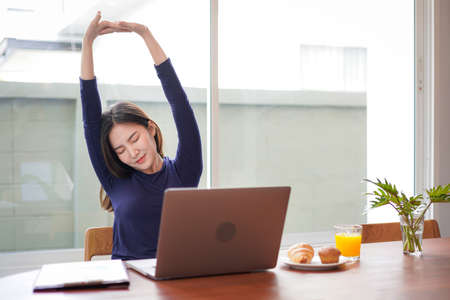 Young asian woman is relaxing to stretching and eating bread with a glass of orange juice while break time after working hard at home 版權商用圖片