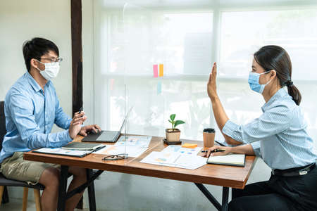 Two business colleagues wearing face mask to brainstorming business project and giving high five to each other while working together with table shield plastic partition to keep social distancing in office