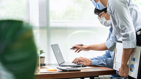 Asian business woman pointing on laptop screen to share idea about new project business to partner while wearing protective face mask to protect coronavirus and brainstorming together