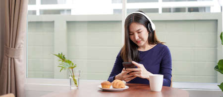 Young asian woman with headphone listening to music and watching video on smartphone while sitting to eating bread with coffee at home