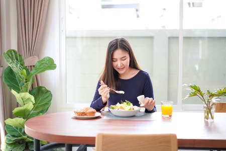 Young asian woman use a salad dressings spoon to mixing with fresh vegetable and drinking orange juice on wellness lifestyle for breakfast with healthy meal at home