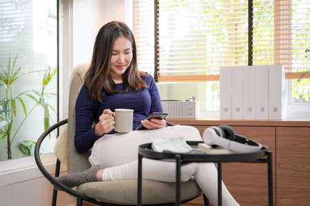 Young asian woman using smartphone to chatting with friend and shopping online while holding coffee cup and sitting to rest on comfortable armchair in living room