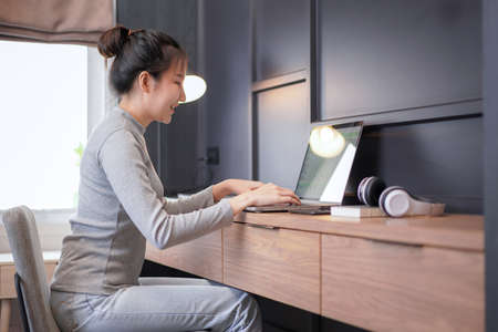 Young asian woman in casual clothes looking on laptop screen and typing financial project about online business on laptop while relaxation and working in cozy workplace at home 版權商用圖片