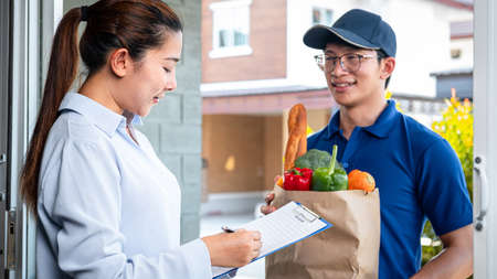 Asian woman customer order food delivery online and standing in front of the house to receive grocery of food, fruit, vegetable and sign on food delivery bill from courier