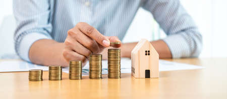 Asian business man putting coin increase on coins stacking with house model while preparation to saving for property investment and house mortgage