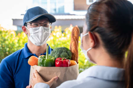 Woman customer in medical face mask standing at the house to accepting a grocery bag of food, fruit, vegetable from asian delivery man in face mask that service delivery during covid-19 pandemic