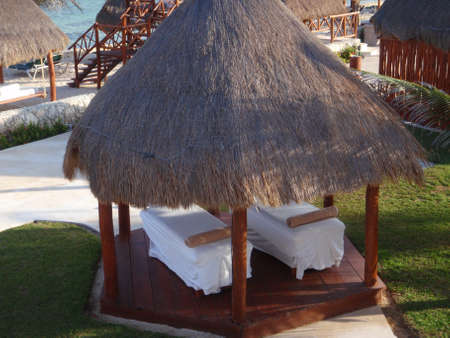 his and hers massage at mexico resort under thatch hut on the beach Editöryel