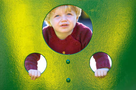Young boy or toddler looking through holes in a colourful wall in a playground and smiling photo