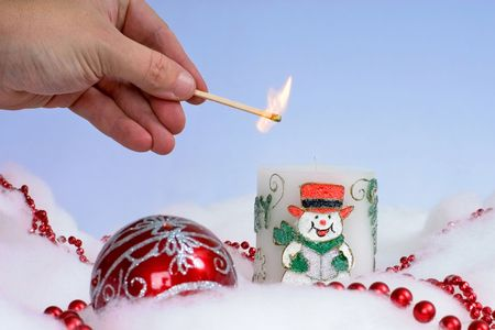 Person lighting cheerful Christmas candle with festive decorations around it and plain background photo