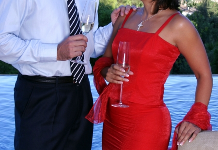 Smartly dressed couple chatting over Champage at a dinner party next to a swimming pool Stock Photo - 2056282