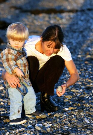 Young mother and toddler son playing on the beach collecting pebbles at sunset in Spain photo