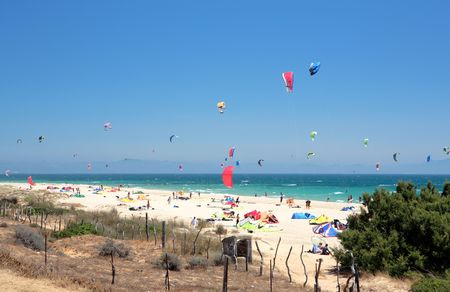 Beautiful white Tarifa beach in Spain packed with kitesurfers and sunbathers photo