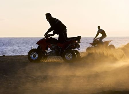 throw up: Lads on quad bikes on sandy beach in Spain during golden sunset Stock Photo