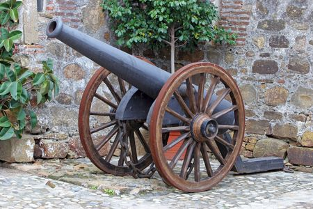 spoked: Antique cast iron Canon with spoked wheels in a castle courtyard in Spain