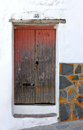 Old wooden padlocked door with peeling red paint on an old Spanish street.