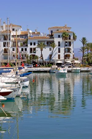 sol: Beautiful white luxury boats and yachts moored in front of bars and apartments in Duquesa port in Spain on the Costa del Sol