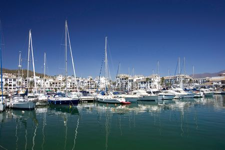 sol: Beautiful white luxury boats and yachts moored in Duquesa port in Spain on the Costa del Sol Stock Photo
