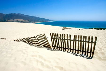Old wooden fence on deserted white sandy beach dunes on a hot sunny day in Tarifa Spain photo