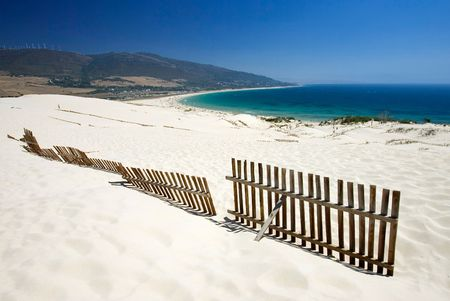 tarifa: Old wooden fence on deserted white sandy beach dunes on a hot sunny day in Tarifa Spain