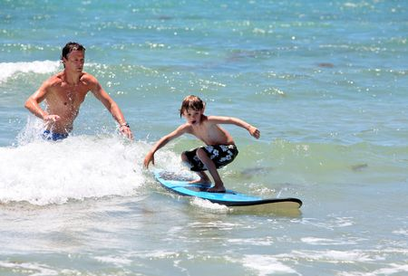 surf wave: Father teaching his young son how to surf in shallow sea on vacation
