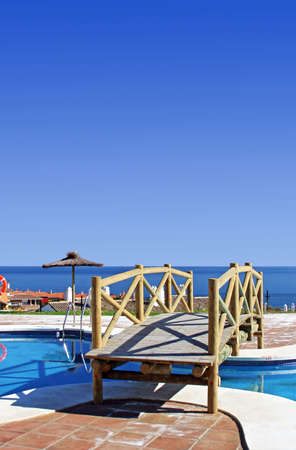 bridged: Wooden bridge over swimming pool in Spanish urbanisation with stunning sea views