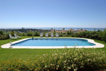 overlooking: Stunning sea views from a large Spanish villa or house as seen from the sunny terrace overlooking a large swimming pool.