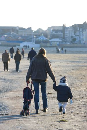 Young woman and toddler son walking on sandy beach in Weymouth, Dorset, UK in winter. Stock Photo - 2060761