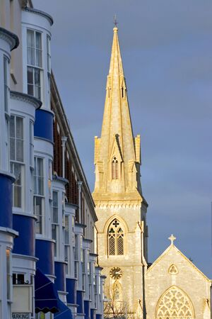 Late afternoon, early evening sun setting on the spire and steeple of church in Weymouth, Dorset in England photo