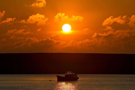 Small fishing boat making its way out to sea during a beautiful golden sunset photo