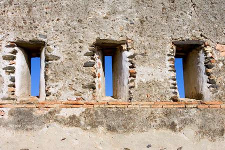 slits: Blue sky peering through slit windows in wall of castle in Fuengirola Spain on the Costa del Sol