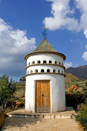 White, cylindrical bird tower or dovecot on sunny Spanish mountainside photo
