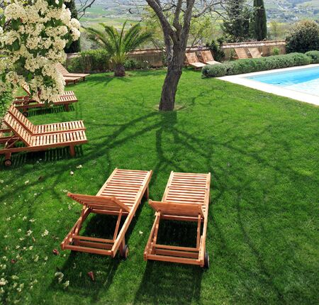 kept: Wooden sunbeds next to a swimming pool in beautiful, green, Spanish garden on a sunny day