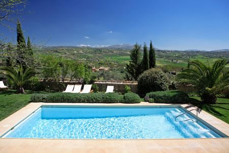 Large rustic hotel and swimming pool set in beautiful gardens in the Spanish countryside with stunning views over the fields below