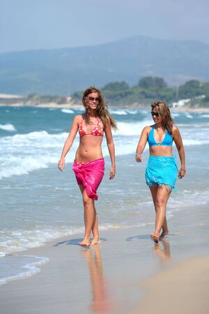Two young, fit, beautiful tanned women walking along sunny, sandy beach whilst on vacation or holiday photo