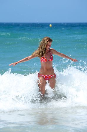splashed: Sexy fit young woman on vacation being splashed by a wave on a sunny beach