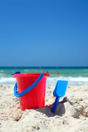 Red bucket and blue spade on sunny, sandy beach on vacation or holiday  photo
