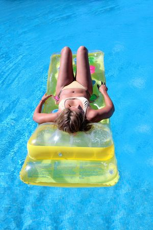 Attractive, slim and tanned young lady lying on inflatable sunbed on sunny swimming pool photo