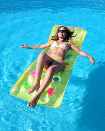 sunbed: Attractive slim and tanned young lady lying on inflatable sunbed on sunny swimming pool on vacation or holiday Stock Photo