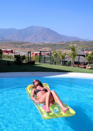 Attractive slim and tanned young woman lying on inflatable sunbed on sunny swimming pool on vacation or holiday with mountains in the background photo