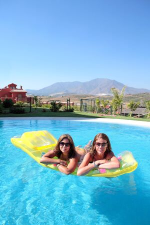 Two girlfriends splashing around on an inflatable sunbed and enjoying the sun in a swimming pool whilst on vacation or holiday Stock Photo