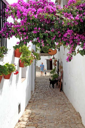 pueblo: Grandfather and Grandson in narrow cobbled streets of colourful white Pueblo on vacation in Spain Stock Photo