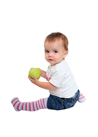 behave: Isolated photo of young, cute baby girl with brown hair sitting down eating fresh green apple or fruit wearing stripey tights