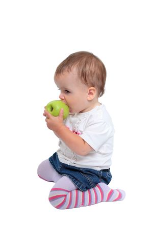 behave: Isolated photo of young, cute baby girl with brown hair kneeling down eating fresh green apple or fruit wearing stripey tights Stock Photo
