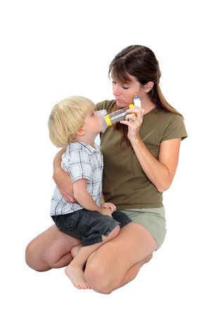 administer: Isolated photo of young mother giving respiratory medicine to her son with bronchitis or chest problems