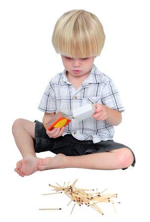 lucifers: Jonge jongen speelde met een doosje lucifers van de veiligheid op een witte achtergrond Stockfoto