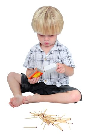 Young boy playing with a box of safety matches on a white background