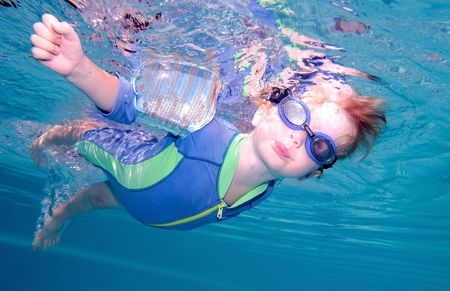 swimming pool float: Young boy or child swimming underwater and holding breath with goggles on Stock Photo